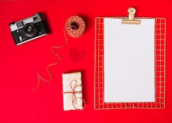 Flache Lage von Fotokamera und leerem Papier