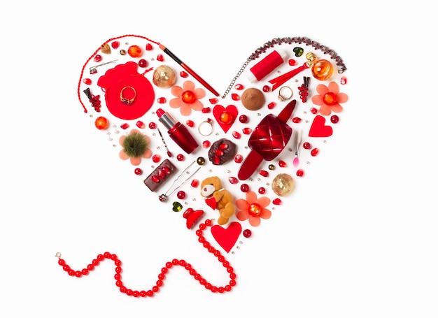 Flache lage von frauen-gizmos in form eines roten herzens - perlen, lippenstift, haarnadeln, parfüm, ringe, süßigkeiten, perlen und grant-körner