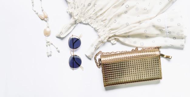 Flache lage von frauenkleidern und -zubehör stellte mit gläsern, handtasche ein.