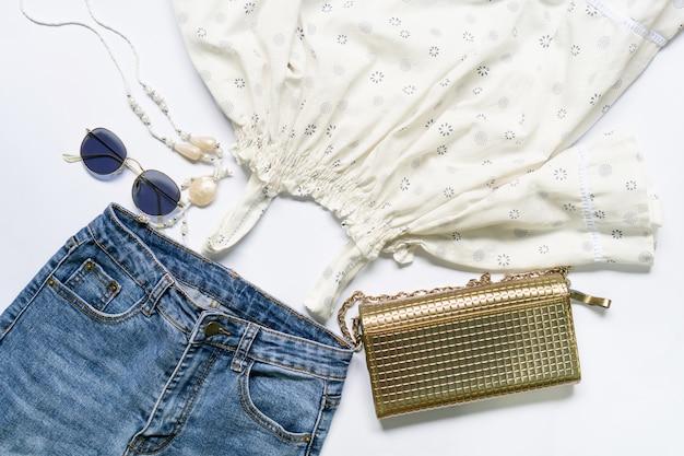 Flache lage von frauenkleidung und -zubehör stellte mit gläsern, handtasche ein.