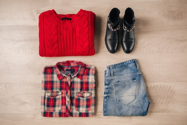 Flache lage von frauenstil und accessoires, roter strickpullover, kariertes hemd, jeans, schwarze lederstiefel, herbstmodetrend, blick von oben, kleidung