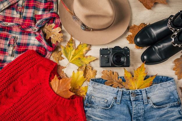 Flache lage von frauenstil und accessoires, roter strickpullover, kariertes hemd, jeans, schwarze lederstiefel, hut, herbstmodetrend, blick von oben, kleidung, gelbe blätter