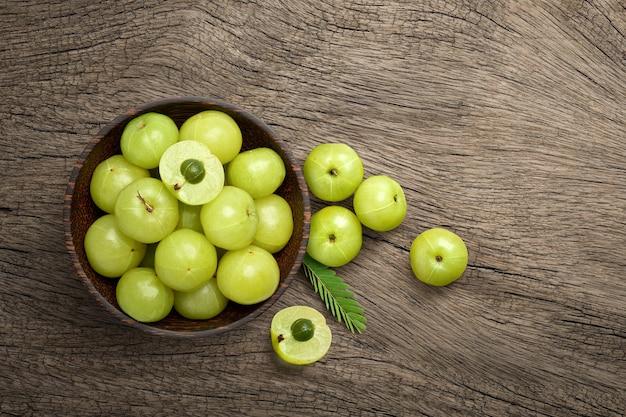 Flache lage von frischen amla (indische stachelbeeren) früchten auf alter holzoberfläche