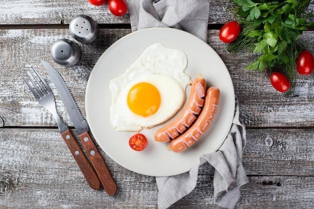 Flache lage von frühstückswürsten und -ei auf platte mit tomaten und tischbesteck