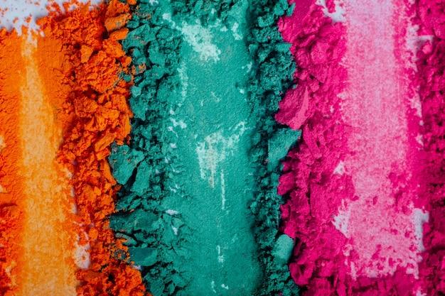 Flache lage von gebrochenem hellem mehrfarbigem lidschatten als muster und muster von kosmetischen schönheitsprodukten einzeln auf weißem hintergrund.