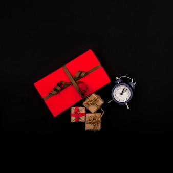 Flache lage von geschenken und von uhr auf schwarzem hintergrund