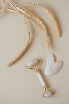 Flache lage von gua-sha-massagerolle und steinschaberwerkzeug und trockene pflanze auf neutralem beige