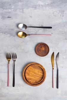 Flache lage von hölzernen platten- und tischbesteckgeräten auf grau. leere platte. , essen, kein abfall.