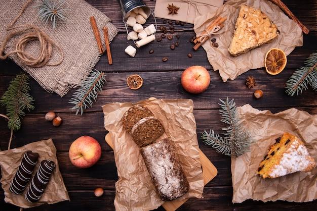Flache lage von kuchen und schokoladendesserts mit kiefer und äpfeln
