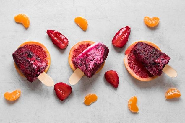 Flache lage von leckerem eis am stiel mit erdbeere und orange