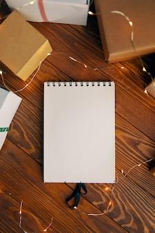 Flache lage von leeren notizbuchgirlanden und geschenkboxen auf holztischhintergrund weihnachten neujahr und bi ...