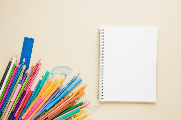 Flache lage von lehrbuch und stiften