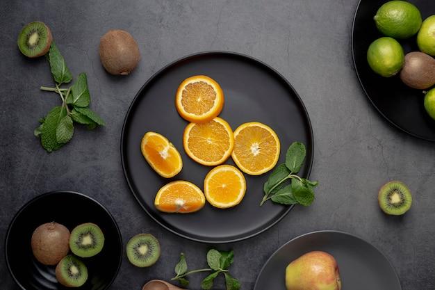 Flache lage von mandarinenscheiben auf platte mit kiwi