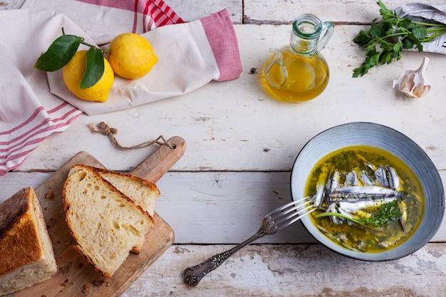 Flache lage von marinierten sardellen in zitronensaft mit olivenöl, knoblauch und petersilie. traditionelles mediterranes sommeressen