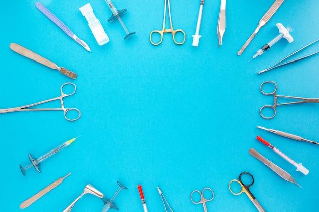 Flache lage von medizinischen instrumenten auf blauem hintergrund. verspotten sie medizinischen hintergrund des gesundheitswesens.