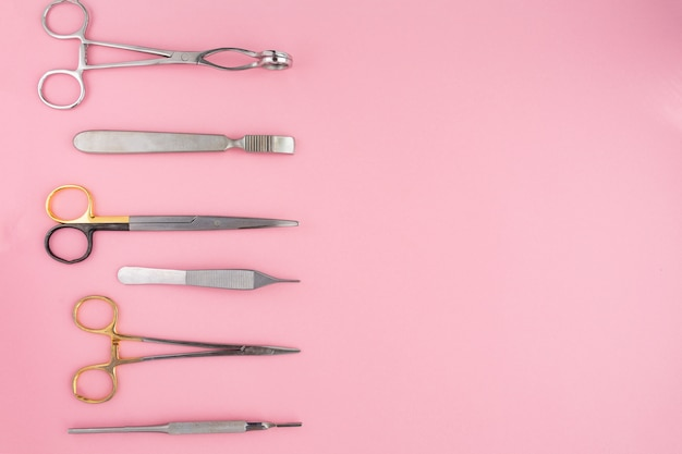 Flache lage von medizinischen instrumenten auf rosafarbenem hintergrund. gesundheitswesen medizinisch.