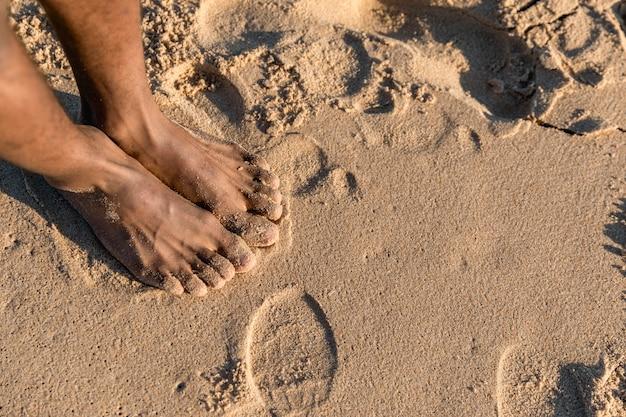 Flache lage von nackten füßen auf sand