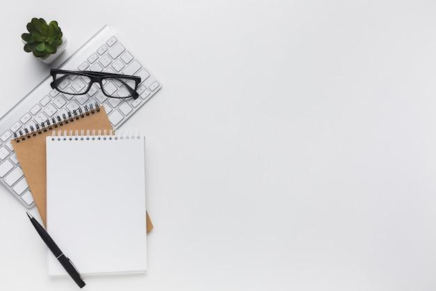 Flache lage von notizbüchern und von gläsern auf dem desktop