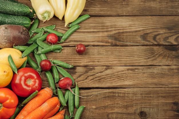 Flache lage von obst, gemüse und kräutern der saison. sommer-food-konzept. gesundes leben und vegetarier, veganer, diät, saubere lebensmittelzutaten. platz für text. essen auf dunklem holzhintergrund.