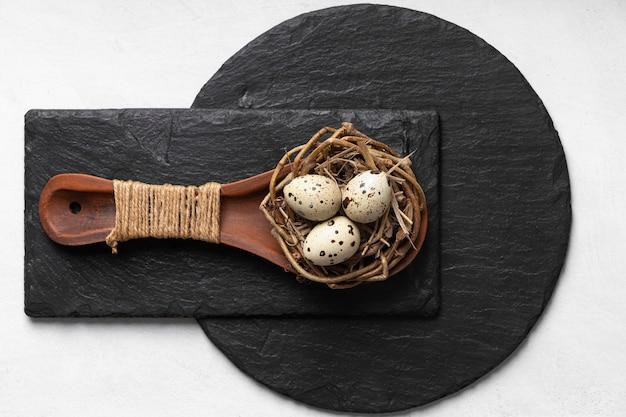 Flache lage von ostereiern in holzlöffel über schiefer