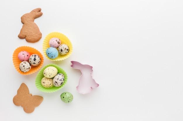 Flache lage von ostereiern mit hasenförmigen keksen und kopierraum