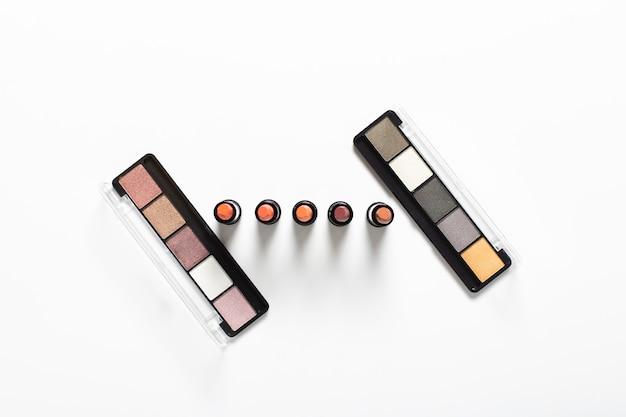 Flache lage von paletten und lippenstiften auf normalem hintergrund