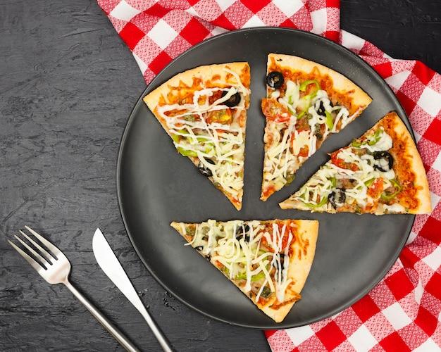 Flache lage von pizzascheiben auf platte