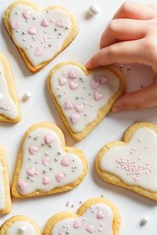 Flache lage von plätzchenherzen mit zuckerglasur und für valentinstag, weißer hintergrund verziert. valentinstag-konzept.