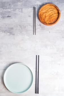 Flache lage von platten- und eisenstöcken auf grau. leere platte. , essen, kein abfall.