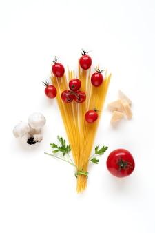 Flache lage von rohen spaghetti-zutaten, die als blumenstrauß auf weißer oberfläche angeordnet sind
