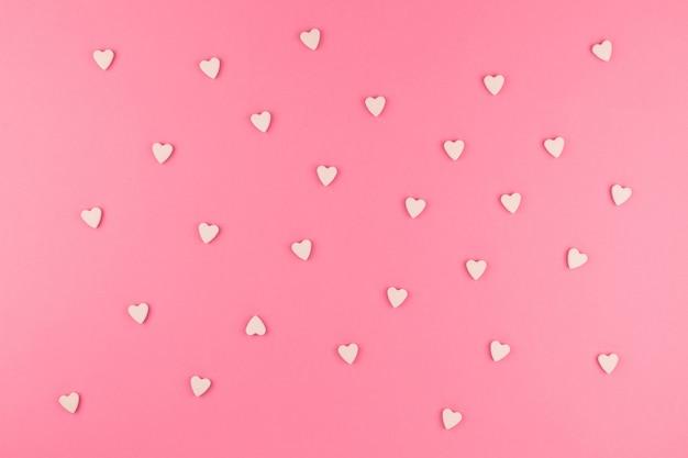 Flache lage von rosa herzförmigen süßigkeiten