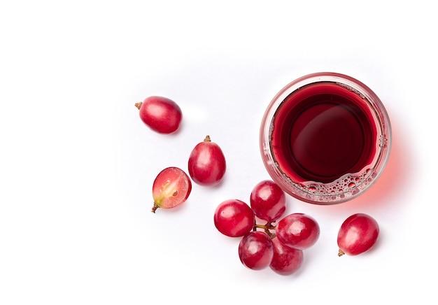 Flache lage von rotem traubensaft mit traubenfrüchten auf weiß