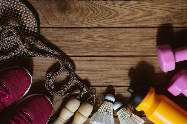 Flache lage von roten sportschuhen, von dummköpfen, von badminton, von flasche wasser und von springseil