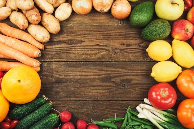 Flache lage von saisonalen früchten, gemüse und kräutern.sommer-food-konzept. gesundes leben und vegetarier, veganer, diät, saubere lebensmittelzutaten. runder rahmen mit platz für text. essen auf dunklem holzhintergrund.
