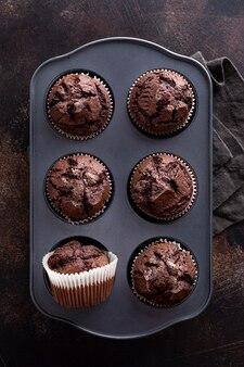 Flache lage von schokoladenmuffins in tablett mit stoff