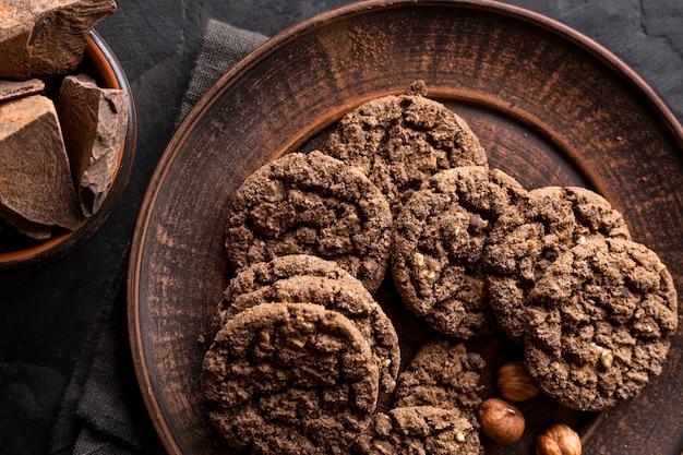 Flache lage von schokoladenplätzchen auf teller mit haselnüssen
