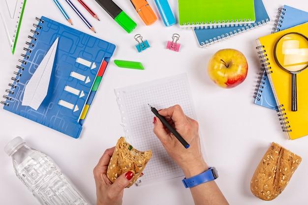 Flache lage von schulmaterial auf einem minimalistischen blauen raum. frau isst sandwich. gesunder snack am büroarbeitsplatz. essen vegane bio-mahlzeiten
