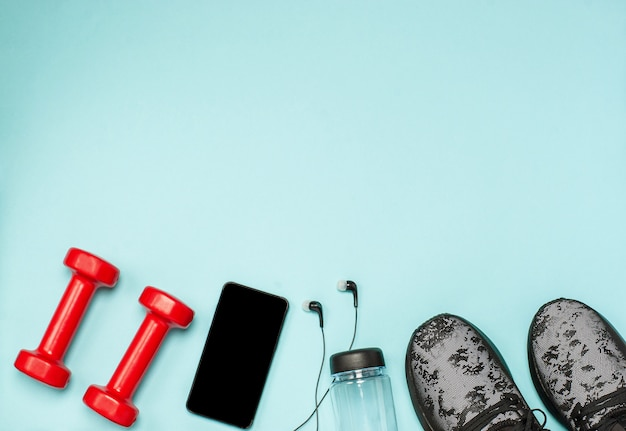 Flache lage von sportgeräten für fitness auf einer blauen oberfläche