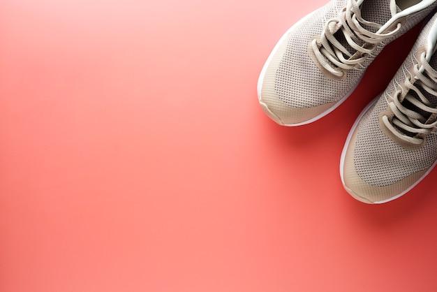 Flache lage von sportschuhen auf einem rosa hintergrund running workout fitness