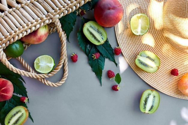 Flache lage von strohhut und tasche mit früchten himbeere, pfirsich, kiwi, limette auf grauer oberfläche im sonnenlicht, sommerzeit. lebensmittelkonzept, kopienraum, draufsicht.