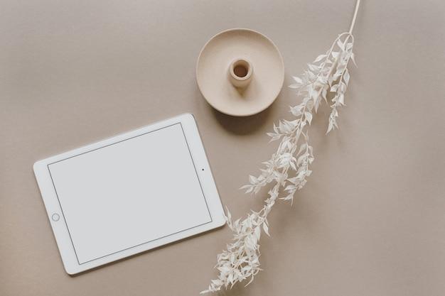 Flache lage von tablet-pad mit leerem bildschirm, weißem blumenzweig, dekorationen auf neutralem pastellbeige. arbeitsbereich für den home-office-schreibtisch. flache lage, draufsicht.