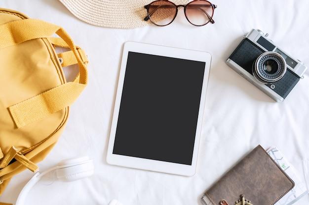 Flache lage von tablet und reiseaccessoires mit strandhut, sonnenbrille, rucksack, kamera
