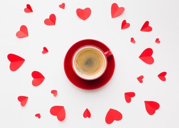 Flache lage von tasse kaffee- und papierherzformen für valentinstag