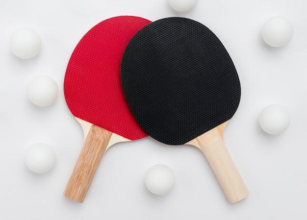 Flache lage von tischtennispaddeln mit bällen