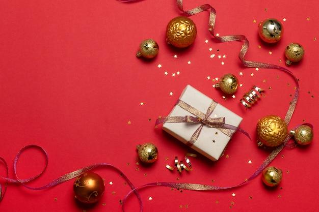 Flache lage von überraschungsgeschenkboxen, goldenes weihnachtsgeometrische bälle, band, funkelnsternkonfettis auf rotem hintergrund mit kopienraum