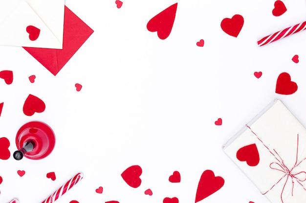 Flache lage von valentinstagherzen mit geschenk und glocke