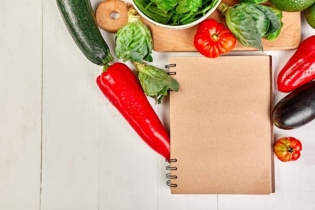 Flache lage von verschiedenem gemüse um kochrezeptbuch