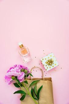 Flache lage von weiblichen kosmetikprodukten und accessoires, geschenkbox und leere karte auf rosafarbenem hintergrund. platz kopieren.