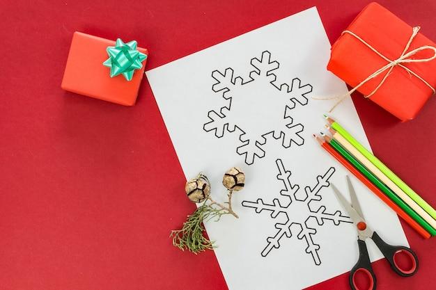 Flache lage von weihnachtsfiguren zum färben und trimmen auf rot