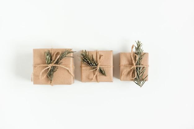 Flache lage von weihnachtshandwerksgeschenkboxen auf der handgemachten braunen papierbox mit weihnachtsbaumzweig. speicherplatz kopieren.